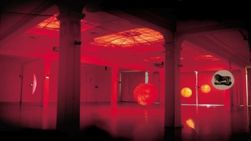 large space covered in red light with several round objects