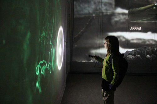 child drawing with torch on light sensitive wall