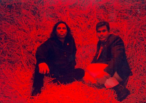two men sitting in a red space of straw
