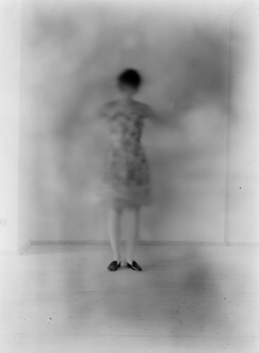 long exposure photograph of woman with her feet in focus and the rest of her body out of focus, b/w photograph