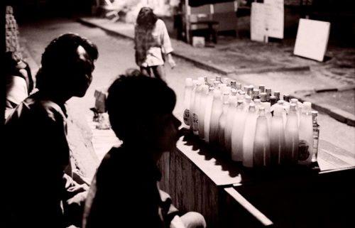 two Javanese boys selling drinks in the street at night
