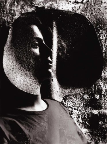 double exposure of female face in front of shovel in sepia colours